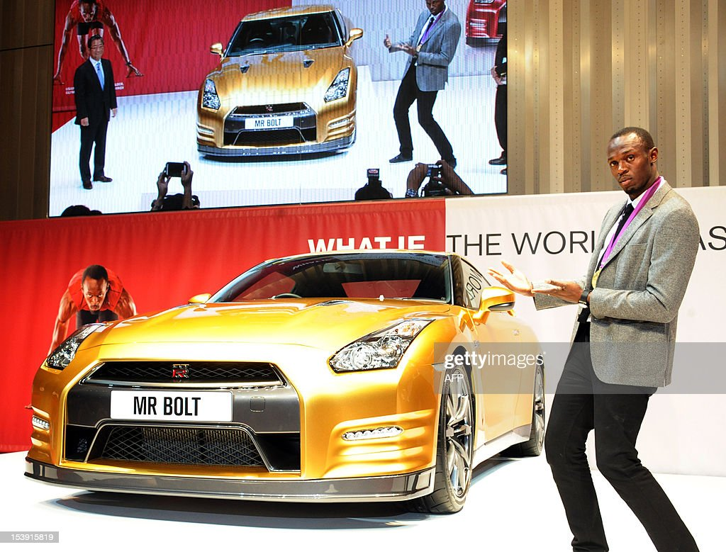 Olympic gold medallist Usain Bolt of Jamaica poses for a photo in front of Japanese auto giant Nissan's gold coloured sports car GT-R at Nissan's headquarters in Yokohama on October 11, 2012. The special coloured GT-R will be auctioned at eBay auction site to benefit the Usain Bolt Foundation supporting youth.