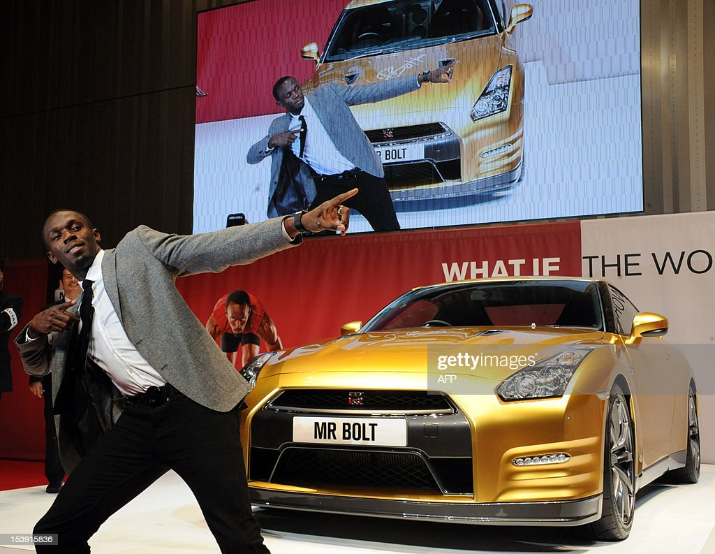 Olympic gold medallist Usain Bolt of Jamaica poses for a photo in front of Japanese auto giant Nissan's gold coloured sports car GT-R at Nissan's headquarters in Yokohama on October 11, 2012. The special coloured GT-R will be auctioned at eBay auction site to benefit the Usain Bolt Foundation supporting youth. AFP PHOTO / RIE ISHII