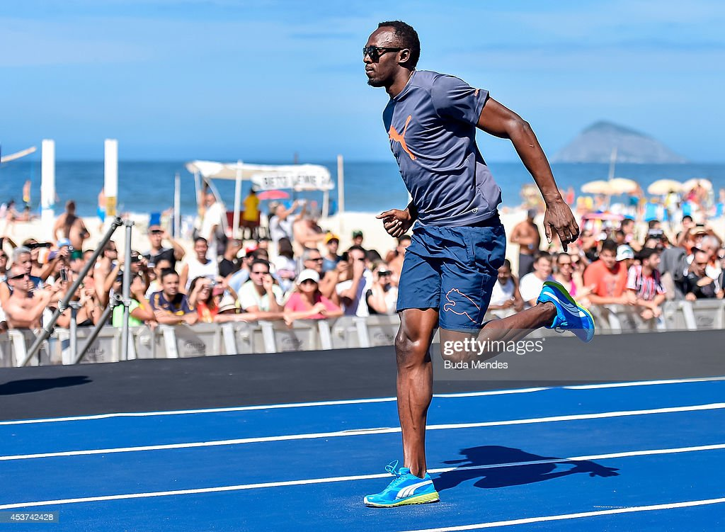Olympic gold medallist <a gi-track='captionPersonalityLinkClicked' href=/galleries/search?phrase=Usain+Bolt&family=editorial&specificpeople=604196 ng-click='$event.stopPropagation()'>Usain Bolt</a> of Jamaica warms up prior to the 'Mano a Mano' Men's 100m challenge at Copacabana beach on August 17, 2014 in Rio de Janeiro, Brazil.