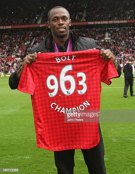 Olympic gold medallist Usain Bolt poses on the pitch ahead of the Barclays Premier League match between Manchester United and Fulham at Old Trafford...