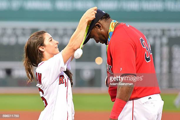 Olympic gymnast Aly Raisman puts a medal on David Ortiz of the Boston Red Sox before throwing out a ceremonial first pitch before a game against the...