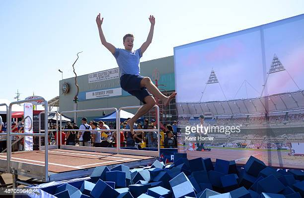 Olympic Ice Dancer Gold Medalist Charlie White jumps into a foam pit while participating in the Long Jump station at the USOC Road to Rio Tour on...