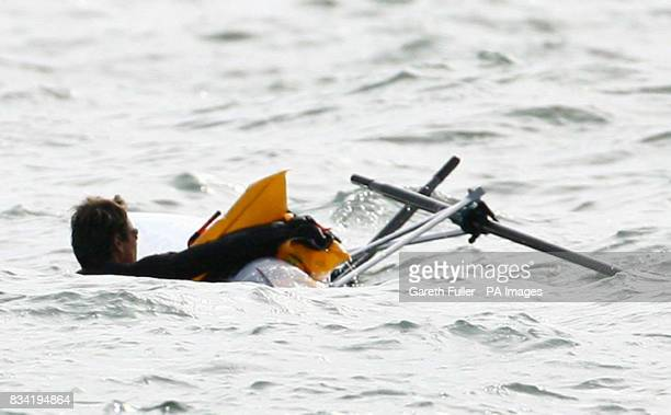 Olympic rower James Cracknell holds onto his boat after capsizing in his first attempt to leave Shakespeare Beach in Dover Kent on the first leg of...
