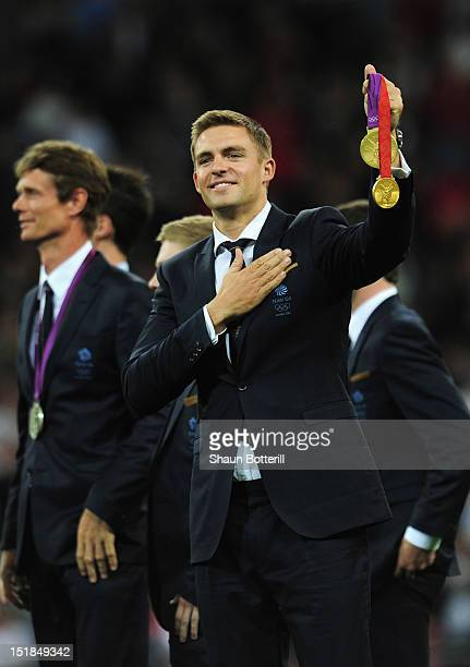 Olympic rowing gold medallist Pete Reed of Great Britain salutes the crowd at half time during the FIFA 2014 World Cup Group H qualifying match...