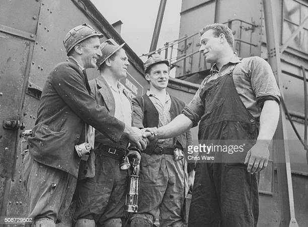 Olympic shot putter Arthur Rowe shaking hands with a group of miners as they start their shift as he prepares to leave for Sweden to compete in the...