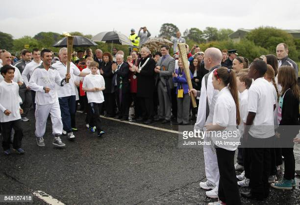 Olympic silver medal winning boxer Michael Carruth waits to receive the flame from Olympic gold medal winner Wayne McCullough during the ceremony to...