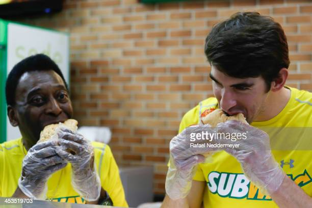 Olympic swimmer Michael Phelps and Pele eat sandwiches as they attend a Subway press conference to promote healthy living and lifestyle among...