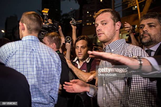 S Olympic swimmers Gunnar Bentz and Jack Conger are mobbed by the media and onlookers while leaving the police station after questioning on August 18...