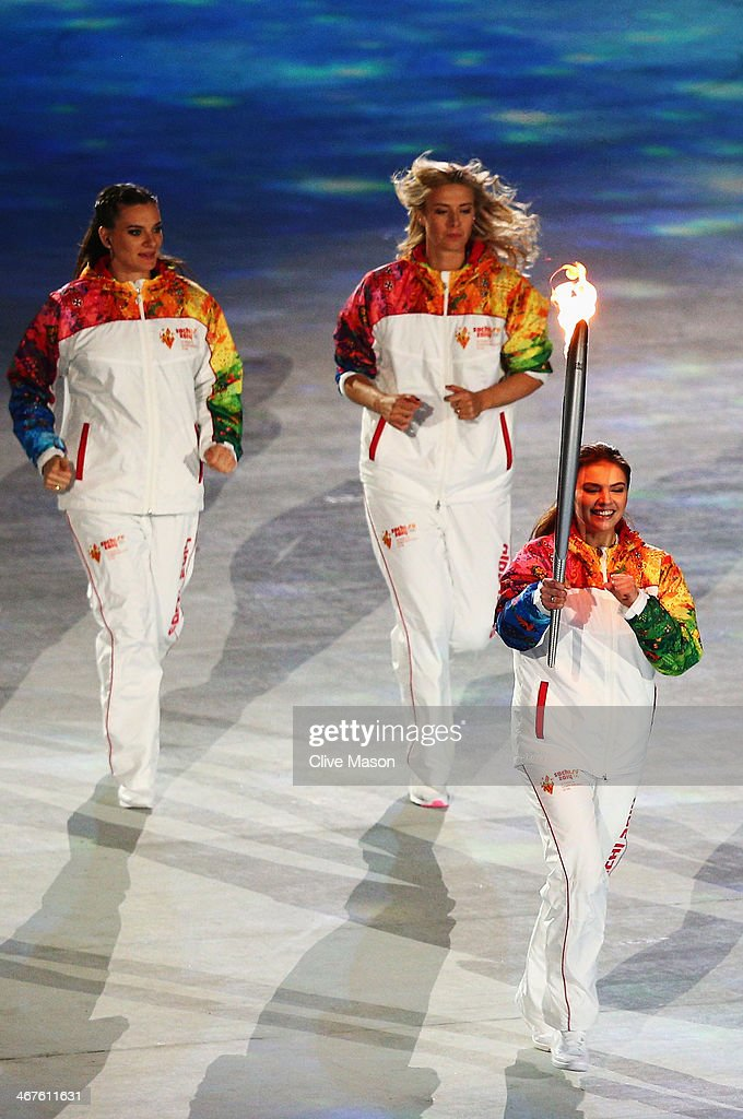 Olympic torch bearer <a gi-track='captionPersonalityLinkClicked' href=/galleries/search?phrase=Alina+Kabaeva&family=editorial&specificpeople=633246 ng-click='$event.stopPropagation()'>Alina Kabaeva</a> carries the torch with Maria Sharapova (C) and <a gi-track='captionPersonalityLinkClicked' href=/galleries/search?phrase=Elena+Isinbaeva&family=editorial&specificpeople=3230101 ng-click='$event.stopPropagation()'>Elena Isinbaeva</a> (R) during the Opening Ceremony of the Sochi 2014 Winter Olympics at Fisht Olympic Stadium on February 7, 2014 in Sochi, Russia.