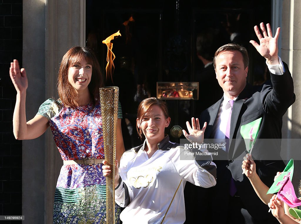 Olympic torch bearer Kate Nesbitt (C) stands with Prime Minister <a gi-track='captionPersonalityLinkClicked' href=/galleries/search?phrase=David+Cameron+-+Politician&family=editorial&specificpeople=227076 ng-click='$event.stopPropagation()'>David Cameron</a> and his wife <a gi-track='captionPersonalityLinkClicked' href=/galleries/search?phrase=Samantha+Cameron&family=editorial&specificpeople=624344 ng-click='$event.stopPropagation()'>Samantha Cameron</a> in Downing Street on July 26, 2012 in London, England. The torch relay will end tomorrow with it's arrival at the Olympic Park for the opening ceremony of the London 2012 Games. (Photo by Peter Macdiarmid/Getty Image