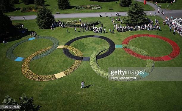 Olympic torch bearer Paul Woodham runs past a floral Olympic rings logo at The Royal Botanic Gardens Kew on July 24 2012 in London England Day 67 of...