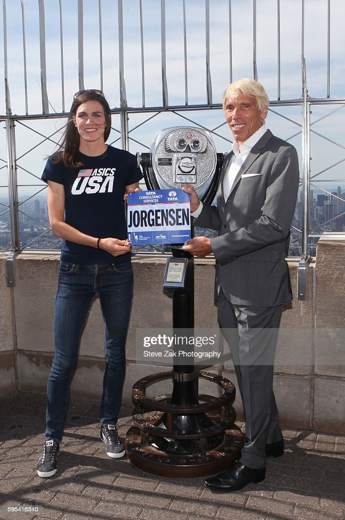 Olympic triathlon gold medalist Gwen Jorgensen accepts her race bib from New York Road Runners President Peter Ciaccia at The Empire State Building on August 25, 2016 in New York City.