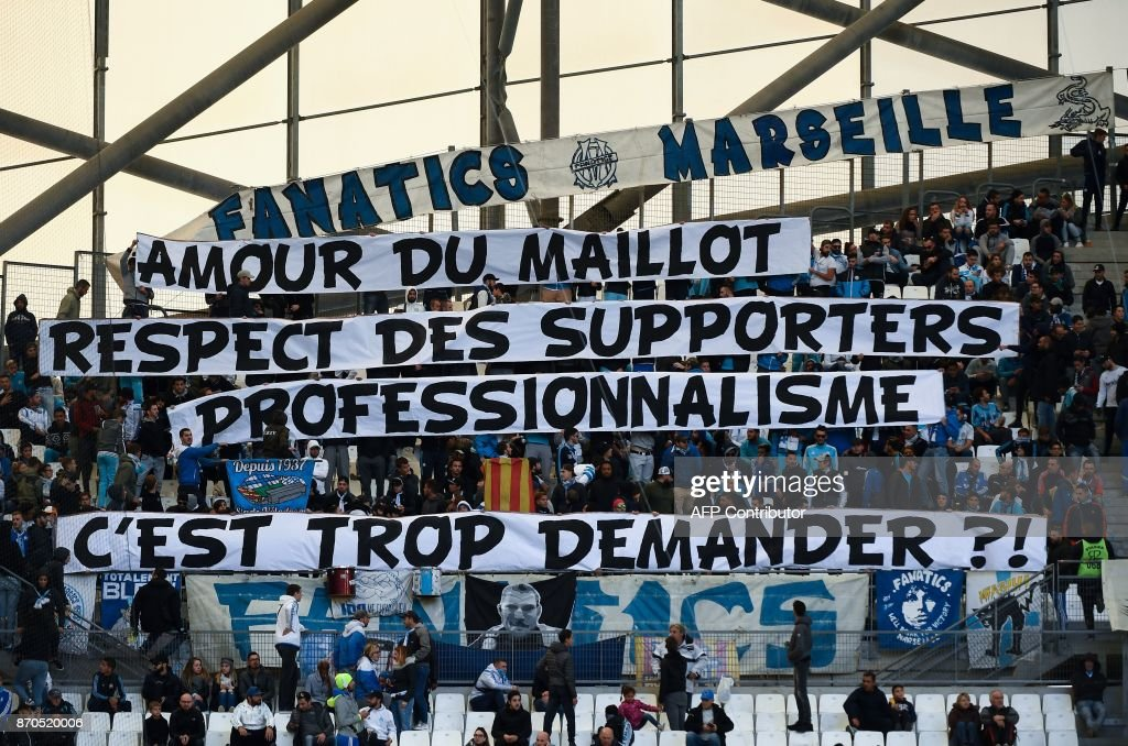 TOPSHOT - Olympique de Marseille (OM) fans hold a banner reading 'for the love of the OM jersey, the respect of fans and professionalism, is it too much to ask?', prior to the start of the French L1 football match between Olympique de Marseille (OM) and Caen at the Velodrome stadium in Marseille on November 5, 2017. Marseille, in fifth, host Caen at the Velodrome in an atmosphere made tense after Patrice Evra was suspended by the club for aiming a karate kick at the head of one of his team's own supporters. /