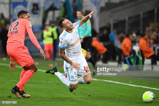Olympique de Marseille's Argentinian forward Lucas Ocampos falls as he vies with Caen's French forward Sylvio Ronny Rodelin during the French L1...
