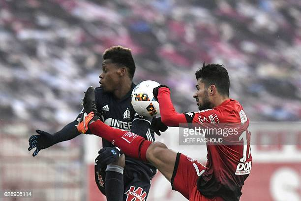 Olympique de Marseille's Cameroonian forward Clinton Njie vies with Dijon's FrenchAlgerian midfielder Mehdi Abeid during the French L1 football match...