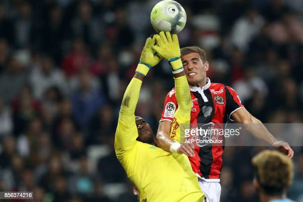 Olympique de Marseille's French goalkeeper Steve Mandanda vies with Nice's French defender Maxime Le Marchand during the French L1 football match...
