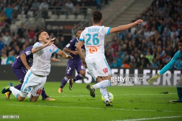 Olympique de Marseille's French midfielder Florian Thauvin scores despite Toulouse's French goalkeeper Alban Lafont next to Olympique de Marseille's...