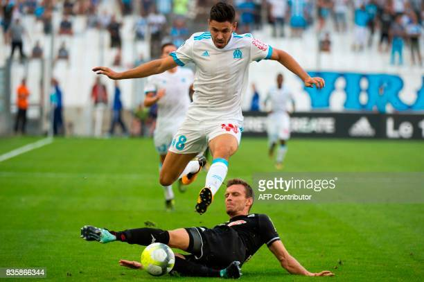 TOPSHOT Olympique de Marseille's French midfielder Morgan Sanson jumps over Angers' French defender Romain Thomas during the French Ligue 1 football...