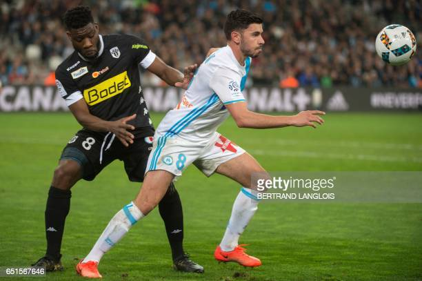 Olympique de Marseille's French midfielder Morgan Sanson vies with Angers' Ivorian defender Ismael Traore during the French L1 football match...