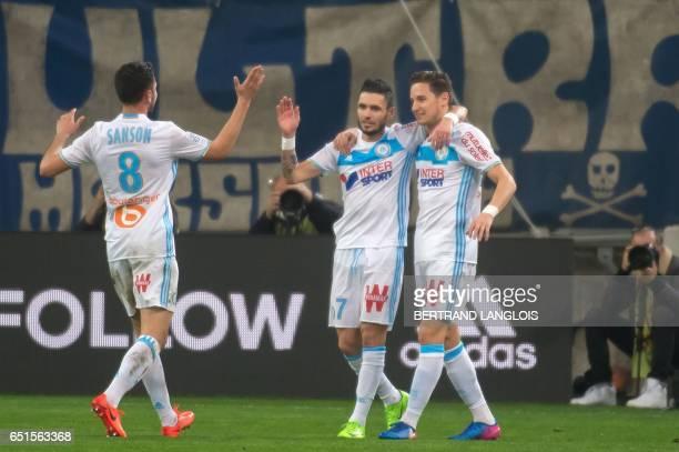 Olympique de Marseille's French midfielder Remy Cabella celebrates with Olympique de Marseille's French midfielder Florian Thauvin and Olympique de...