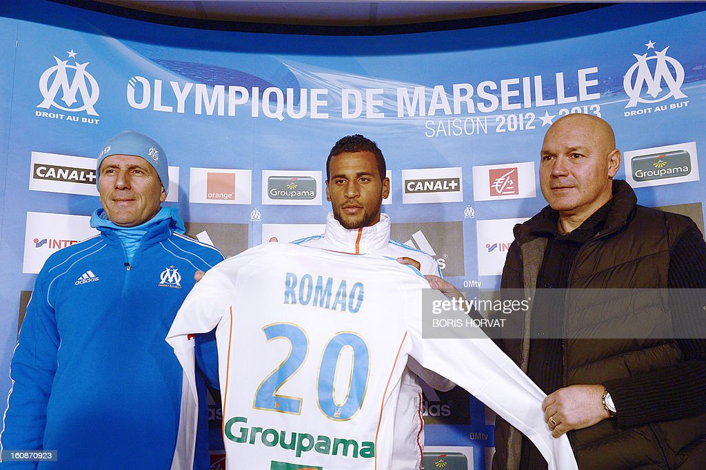 Olympique de Marseille's newly-recruited French-born Togolese midfielder Jacques-Alaixys Romao (C) poses with his new jersey, surrounded by Marseille's head coach Elie Baup (L) and Marseille's general manager Jose Anigo (R), during a press conference as part of his official presentation on February 07, 2013 at the Commanderie stadium in Marseille. Lorient's former midfielder Romao, 29, signed a contract, reported to be for three years and a half, with Marseille.