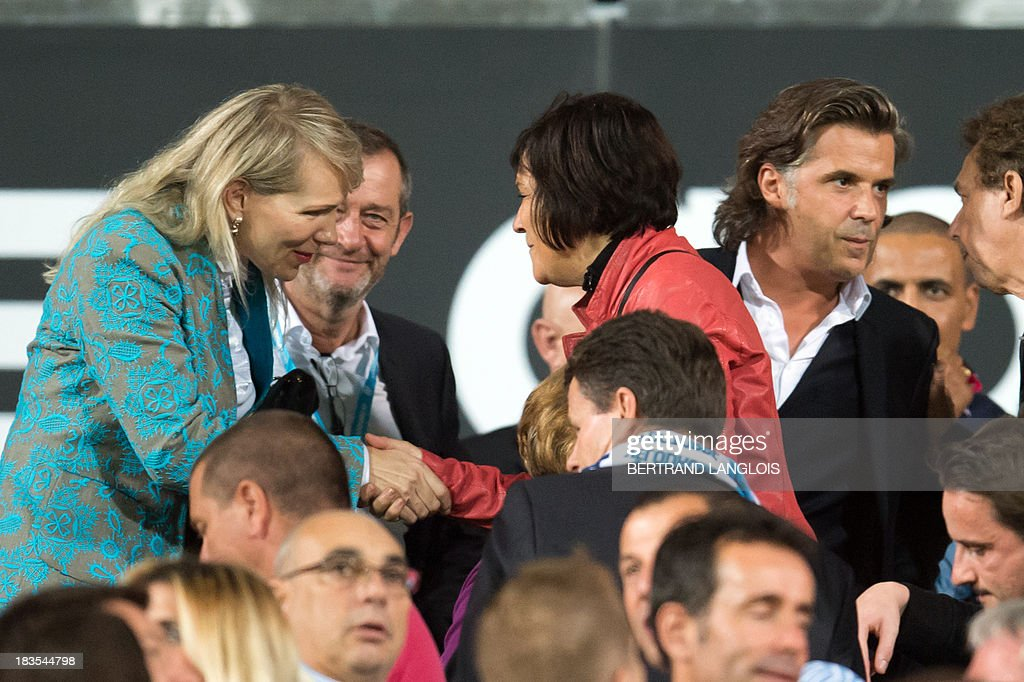 Olympique de Marseille's owner Margarita Louis-Dreyfus (L) shakes hands with French Junior Minister for Disabled People Marie-Arlette Carlotti (C) next to OM's president Vincent Labrune prior to the French L1 football match Olympique de Marseille vs Paris Saint-Germain on October 6, 2013 at the Velodrome stadium in Marseille, southern France. AFP PHOTO / BERTRAND LANGLOIS