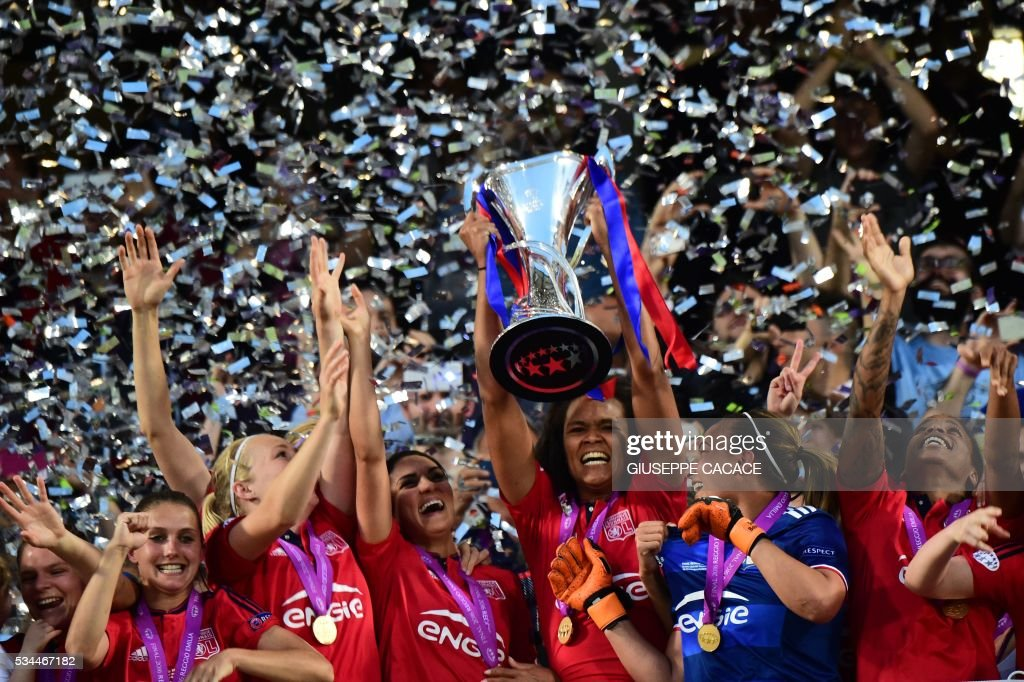 Olympique Lyonnais' captain Wendie Renard holds the trophy and celebrates with teammates after winning the UEFA Women's Champions League Final football match VFL Wolfsburg vs Lyon at the Citta del Tricolore stadium in Reggio Emilia on May 26, 2016. Lyon won the final in the penalty shoot-out (4-3; 1-1) / AFP / GIUSEPPE