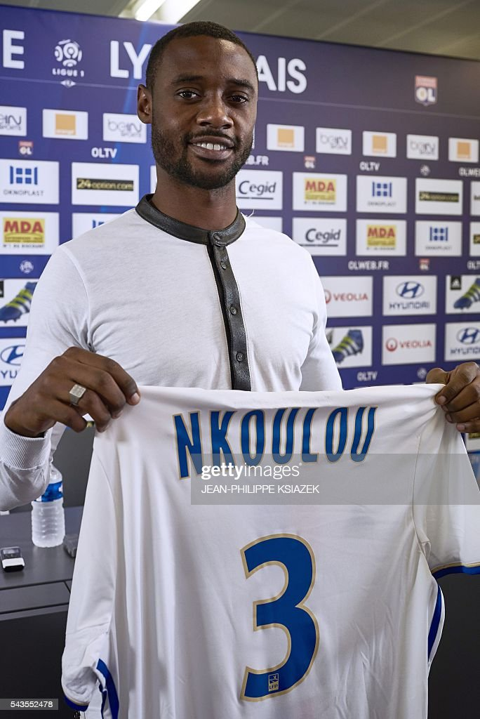Olympique Lyonnais' football club new player cameroonian Nicolas Nkoulou poses with his new jersey during his official presentation in Lyon on June 29, 2016. / AFP / JEAN