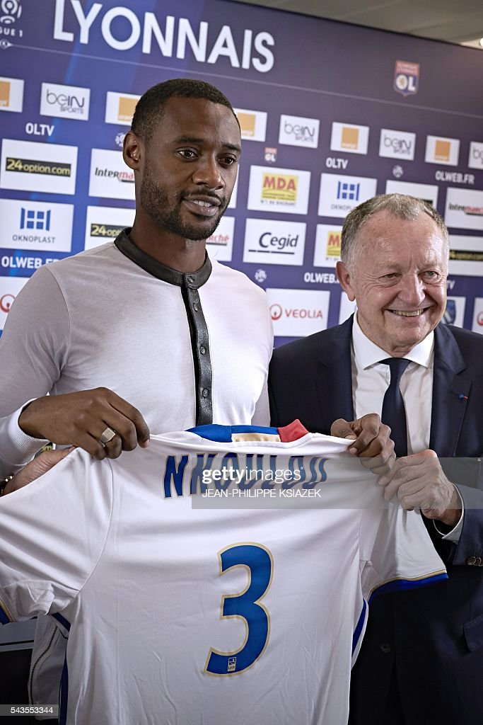 Olympique Lyonnais' football club new player cameroonian Nicolas Nkoulou (L) poses with his new jersey, next to Lyon's president Jean Michel Aulas (R) during his official presentation in Lyon on June 29, 2016. / AFP / JEAN