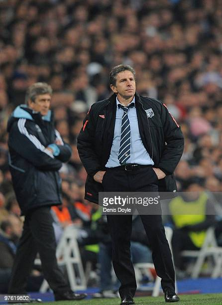 Olympique Lyonnais manager Claude Puel watches his team play Real Madrid beside Real manager Manuel Pellegrini during the UEFA Champions League round...