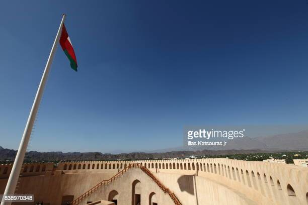 Oman flag in the sandstone fort of Nizwa, with oasis town and the Hajar mountains in the background