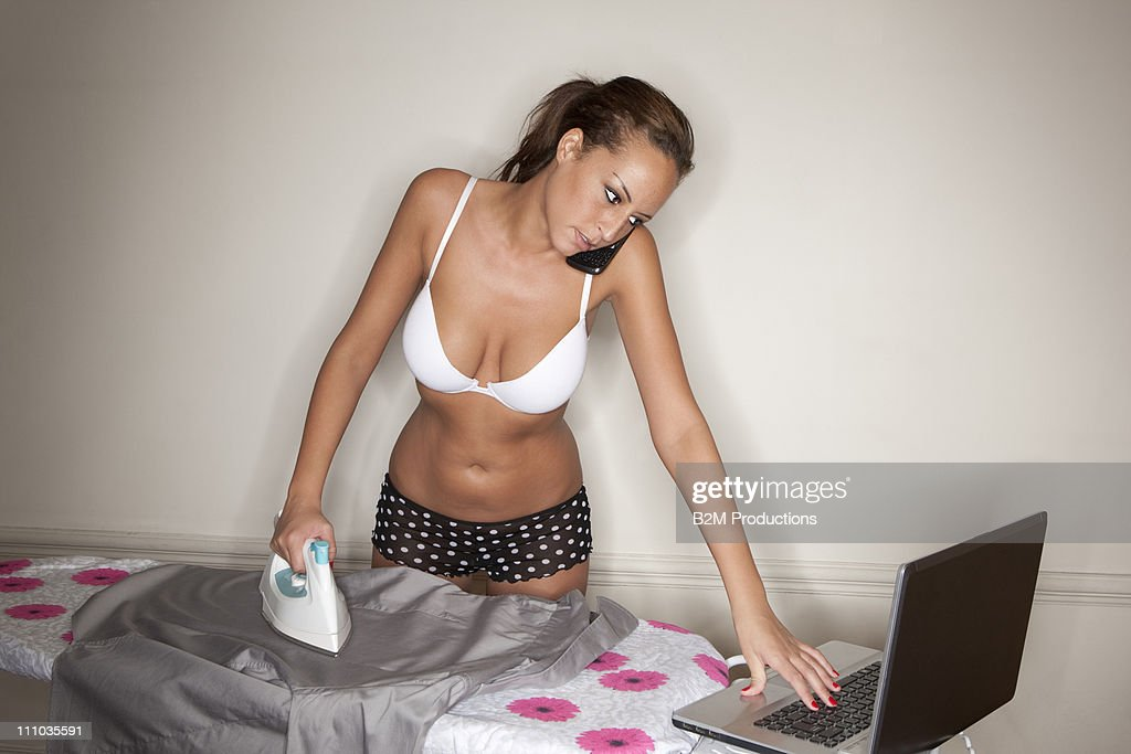 oman ironing shirt and using labtop and cell phone : Stock Photo