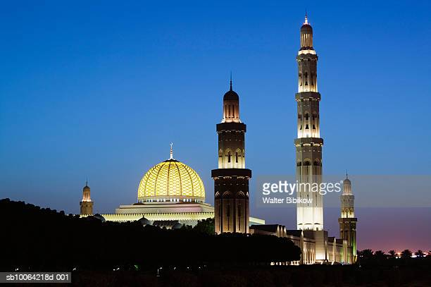 Oman, Muscat-Al-Ghubrah, Grand Mosque exterior illuminated at dusk