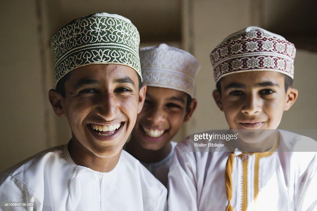 Oman, Western Hajar Mountains, Jabrin Castle, three school boys smiling, portrait