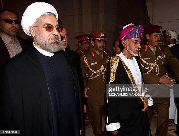 Omani leader Sultan Qaboos bin Said and Iranian President Hassan Rouhani walk during a welcome ceremony in Muscat on March 12 2014 Rouhani arrived in...