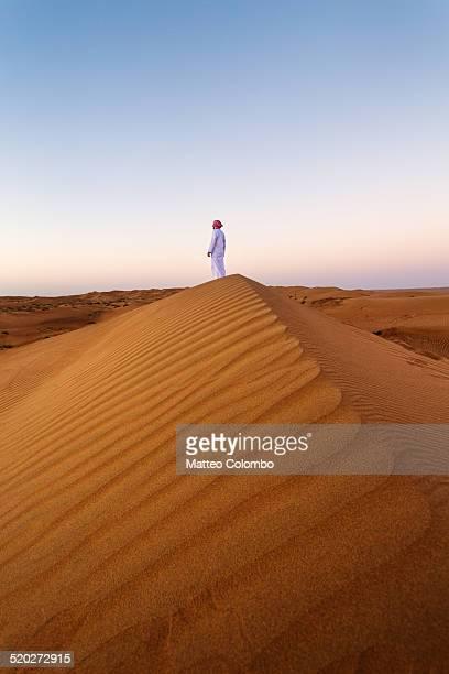 Omani man looking at sunrise in the desert, Oman