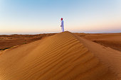 Omani man looking at sunrise in the desert, Oman