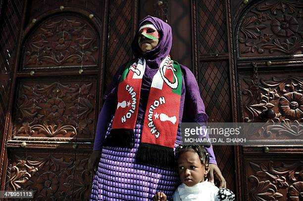 A Omani woman with her daughter watch cyclists at the start point of the forth stage of the 2014 Oman Tour on February 20 between Wadi Al Abiyad and...