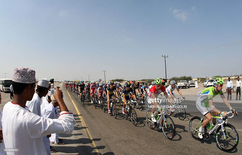 Omanis take pictures of cyclists competing in the third stage of the Tour of Oman, from Nakhal Fort to Wadi Dayqah Dam, on February 13, 2013, in Oman. The six-stage race, which follows the Tour of Qatar, won by Britain's Mark Cavendish last week, culminates on February 16, at Matra Corniche. AFP PHOTO / MOHAMMED MAHJOUB