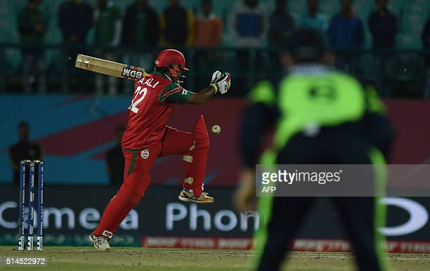 Oman's Aamer Ali is watched by an Ireland fielder as he plays a shot during the World T20 cricket tournament match between Ireland and Oman at The...