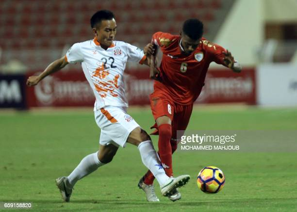 Oman's Raed Saleh fights for the ball against Bhutan's Lhendup Dorjl during their Asian Cup qualifying football match on March 28 2017 at the Sultan...