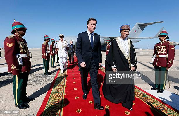 Oman's Sultan Qaboos bin Said walks with Britain's Prime Minister David Cameron after his arrival on December 21 2012 in Muscat Oman Cameron's visit...