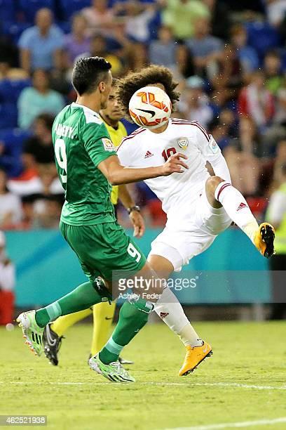 Omar Abdulrahman of United Arab Emirates attempts to kick the ball with Iraq defender Abdulaziz Hussain Haikal of Iraq in frame during the Third...