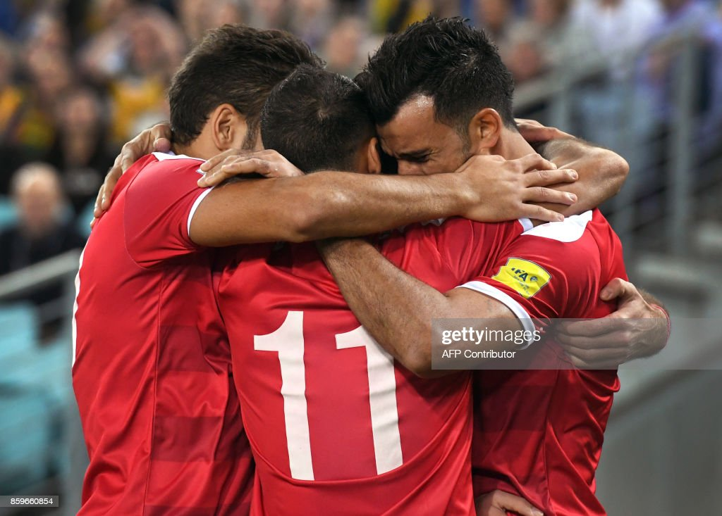 TOPSHOT - Omar Alsoma of Syria is congratulated by teammates as he celebrates scoring against Australia during their 2018 World Cup football qualifying match played in Sydney on October 10, 2017. /