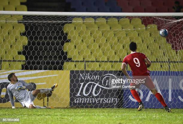 Omar Alsoma of Syria scores his penalty kick past Australian goalkeeper Mathew Ryan during the 2018 FIFA World Cup Asian Playoff match between Syria...
