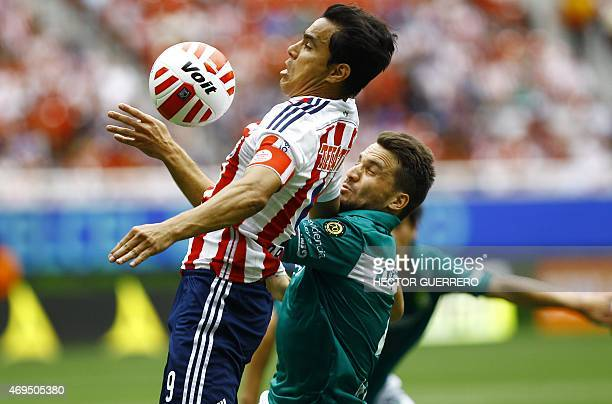Omar Bravo of Chivas vies of the ball with Ignacio Canuto of Leon during their Mexican Clausura 2015 tournament football match at Omnilife stadium in...