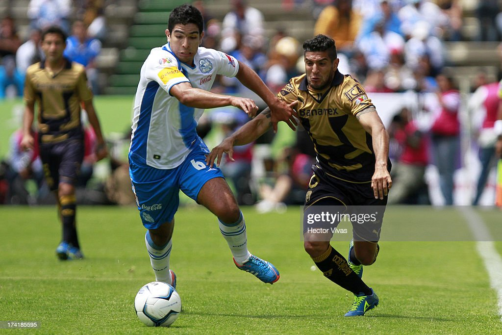 Omar Bravo (R) of Pumas struggles for the ball with Diego de Buen (L) of Puebla during a match between Pumas and Puebla as part of the Torneo Apertura 2013 Liga Mx at Cuauhtemoc Stadium on July 21, 2013 in Puebla, Mexico.
