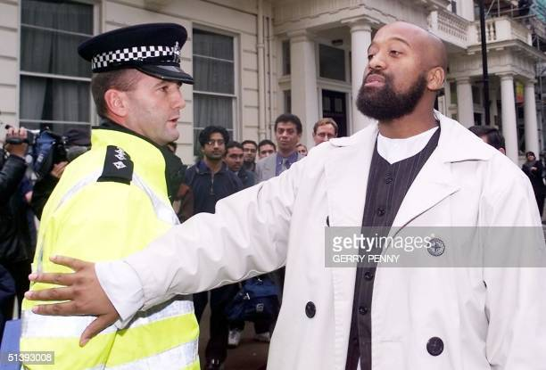 Omar Brookes leader of AlMuhajiroun in London pushes aside a policeman as he delivers his speech outside the Pakistan Enbassy Later protesters...