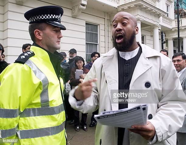 Omar Brookes of AlMuhajiroun in London is closely watched by a policeman as he delivers his speech outside the Pakistan Enbassy 18 September 2001...