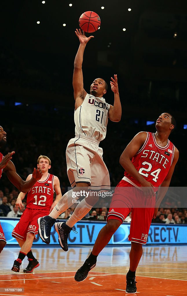 Omar Calhoun #21 of the Connecticut Huskies heads for the net as T.J. Warren #24 of the North Carolina State Wolfpack defends during the Jimmy V Classic on December 4, 2012 at Madison Square Garden in New York City.